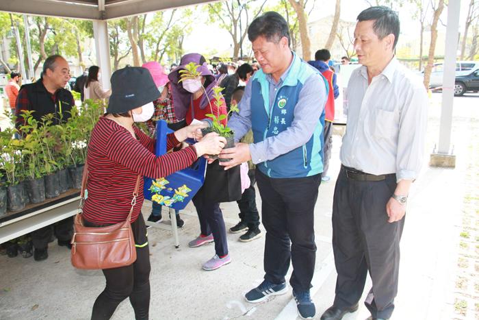 林務所在金寧鄉公所停車場辦理贈苗活動,楊忠俊到場致意,並協助發放給民眾。(李金鎗攝)