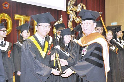 黃奇校長為畢業生進行正冠撥穗及頒發畢業證書。(李金鎗攝)